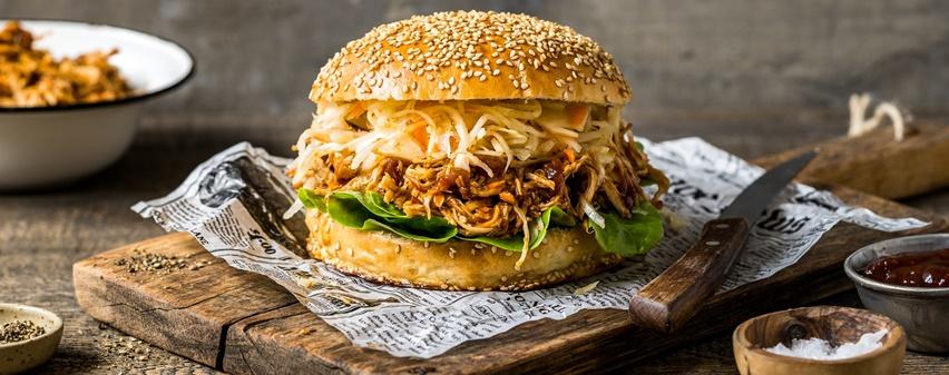 Pulled Chicken Burger auf Holzbrett